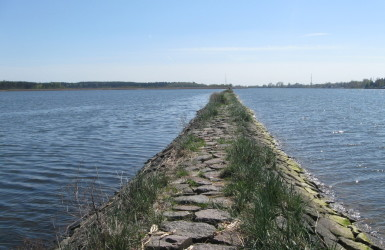 Zabytkowa grobla rozdziela wody Śmiałej Wisły i jeziora Ptasi Raj