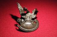 Orzełek z czapki garnizonowej. Wygięcia i nadtopienia powstały wskutek eksplozji bomby lotniczej.