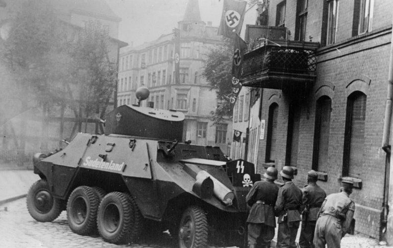 """Bojówkarze SS-Heimwehr Danzig kryją się za wozem pancernym Steyr ADGZ """"Sudetenland"""". Źródło: Bundesarchiv Koblenz."""