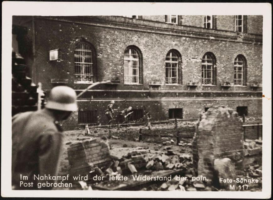 Walka o pocztowy budynek trwa... Na pierwszym planie zniszczone ogrodzenie. Źródło: Muzeum Gdańska.